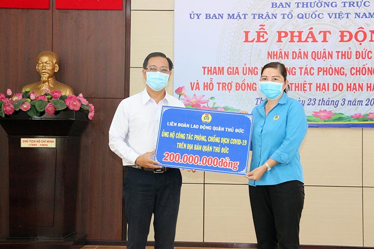 Chủ tịch UB.MTTQ VN quận Hà Tuấn Anh (trái) nhận bảng tượng trưng số tiền đóng góp từ đại diện LĐLĐ quận.