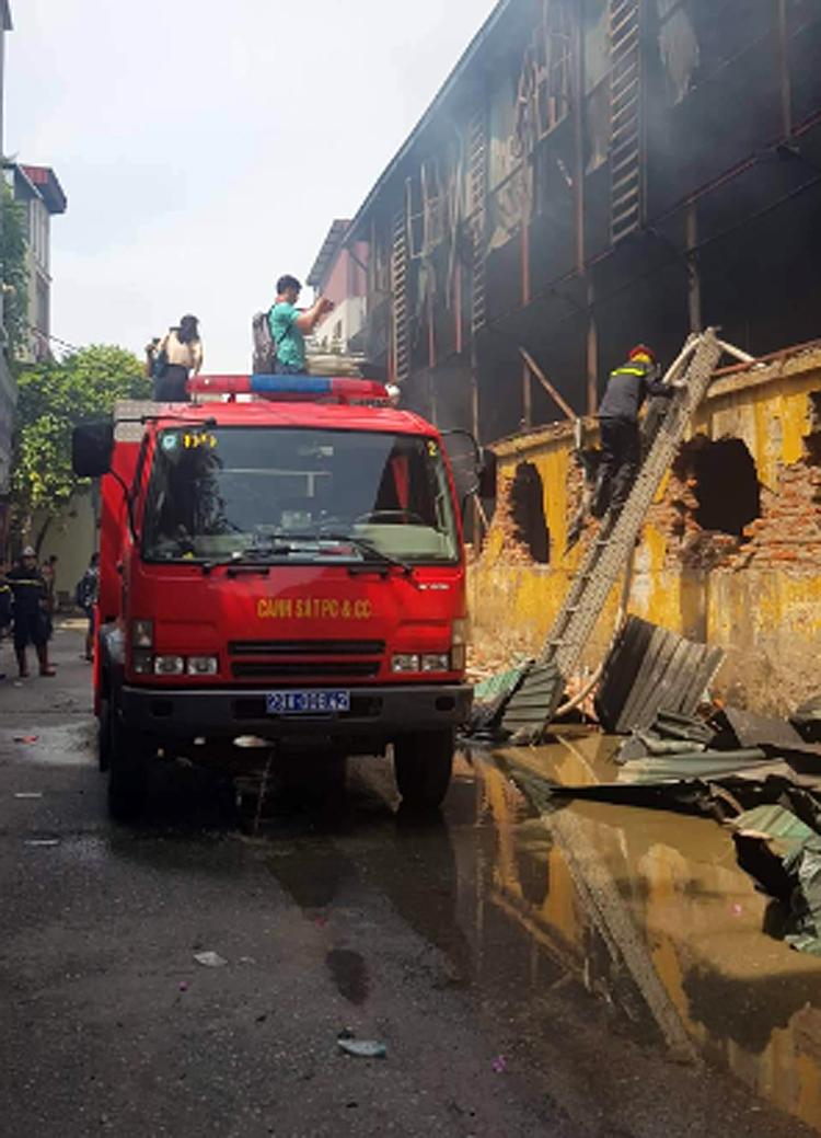 Tác nghiệp tại hiện trường vụ cháy trong những điều kiện không đảm bảo an toàn. Ảnh: Nguyễn Ngân.