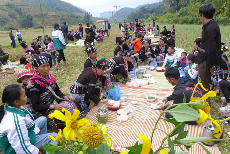 Người dân cùng ăn tết cơm mới chung trên cánh đồng rộng ở cuối bản. Ảnh: T.C