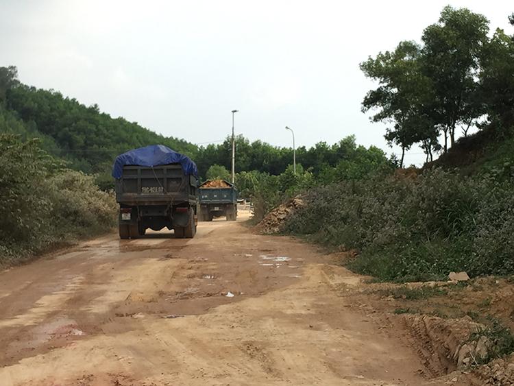 Xe tải chở đầy đất chạy trên đường liên thôn để ra đường 35. Ảnh PV
