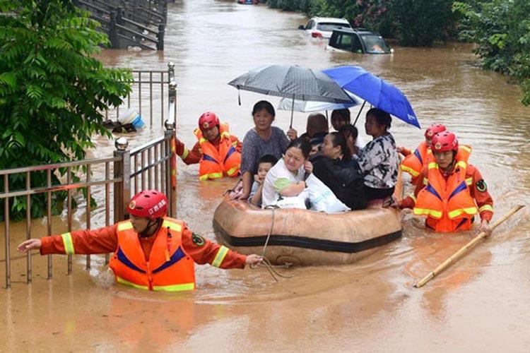 Nhân viên cứu hộ sơ tán người dân đến nơi an toàn tại tỉnh Giang Tây - Trung Quốc hôm 8/7. (Ảnh: EPA)