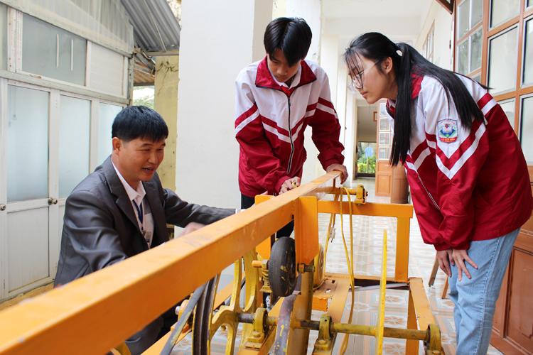 Thầy giáo An Văn Thái cùng các em học sinh bên công trình nghiên cứu khoa học Máy rèn, duỗi kim loại và hợp kim.