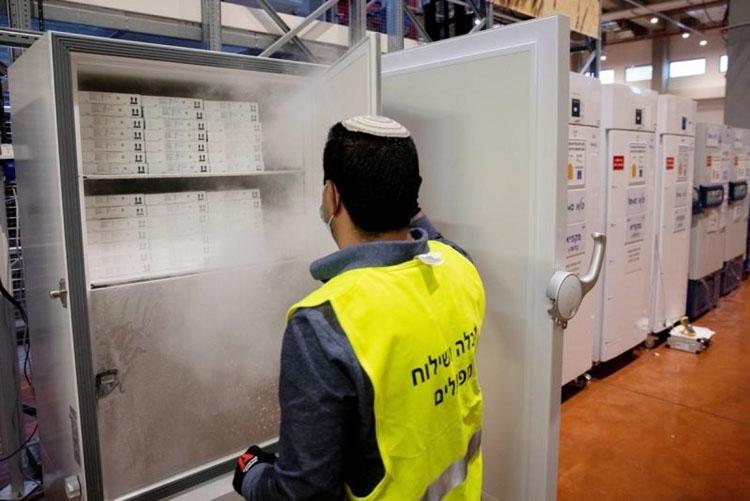 Nhân viên mở tủ chứa vaccine Pfizer/BioNTech tại Israel hồi tháng 1. (Ảnh:Reuters)