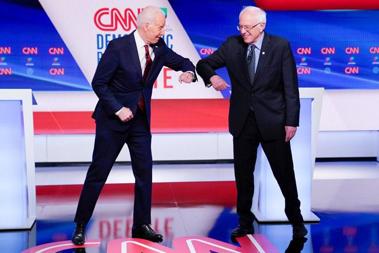 Cú chạm khuỷu tay giữa hai ứng cử viên thay thế cái bắt tay trước khi tranh luận. (Ảnh: REUTERS)