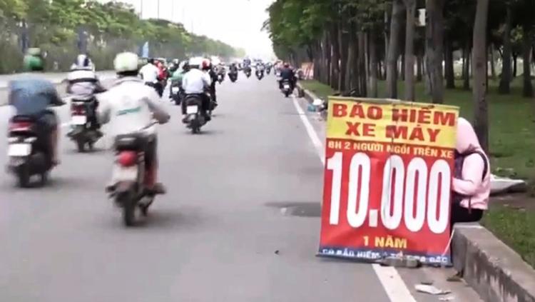 Người dân đi mua bảo hiểm xe máy ngay trên đường. (Ảnh: KT)