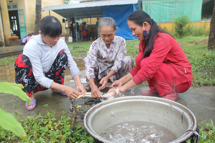 Bà Nguyễn Thị Tám (ngồi giữa) năm nay 80 tuổi mang gà, rau đến ủng hộ bộ đội.