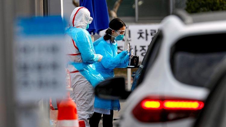 Một nhân viên y tế chuẩn bị lấy mẫu từ một người lái xe qua một trạm xét nghiệm trên đường tại Trung tâm y tế Đại học Yeungnam, Hàn Quốc. Ảnh: Reuters