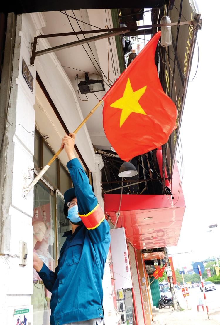 Đội dân quân chỉnh trang lại cờ Tổ quốc trước cửa nhà dân.