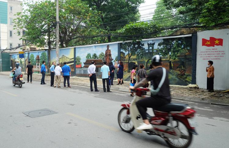 Người dân và các cán bộ phường vui vẻ thưởng lãm tác phẩm tranh tường.