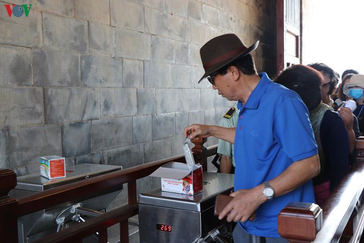 Du khách nhận khẩu trang miễn phí tại Đại Nội Huế.